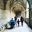 imagen de Familia visitando el Claustro del Monasterio. Uno de los turistas es usuario de silla de ruedas