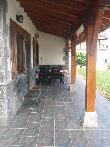 imagen de Porche equipado con mesa y sillas de terraza accesibles en la entrada a la casa.