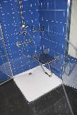 imagen de Detalle de las duchas adaptadas existentes en los 6 baños adaptados completos existentes en el albergue. Todas tienen asiento y barras