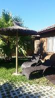 imagen de Terraza de los bungalows con tumbonas y sombrillas al estilo balinés